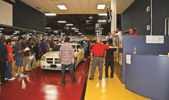 Photography by Chris WolskiDealers bid for cars during a closed sale at South Bay Auto Auction in Gardena, Calif.