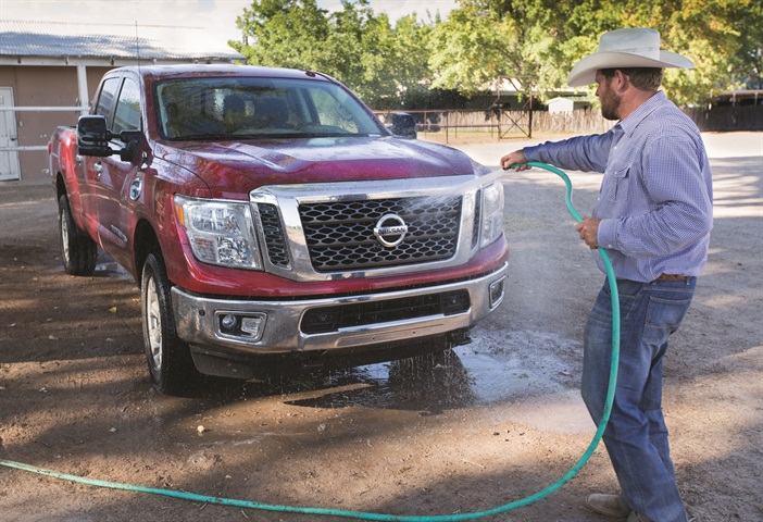 Shain Sproul, a rodeo rider and farmer, washes his three-quarter-ton