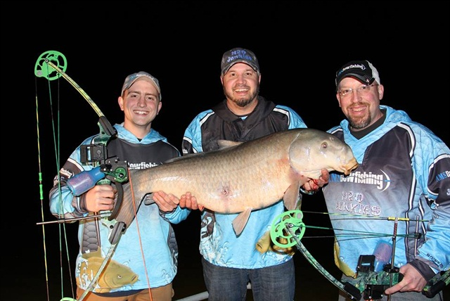Matt Schillinger (center) and two other AMS Bowfishing employees show off their catch.
