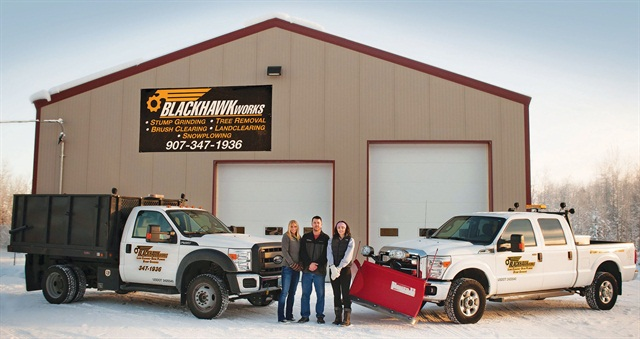 Derek Broderick (center) stands in front of BlackHawk Works' office with his wife and daughter. The company has equipped a F-250 with a snow plow and a F-450 with a chip box. Photo courtesy of BlackHawk Works.