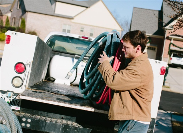 Justin Tullis, an employee of Olympic Pool Plastering, loads equipment onto one of the fleet's propane trucks.