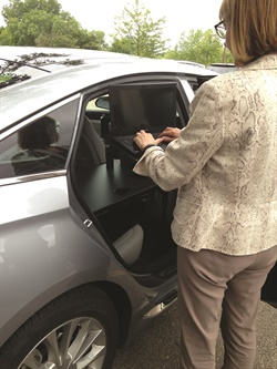 Jill Clark, president of Ergonomic Solutions, demonstrates how the desk can be used standing up outside the vehicle. The desk's arm can be raised or lowered depending on whether you want to sit or stand. Photo courtesy of Ergonomic Solutions.