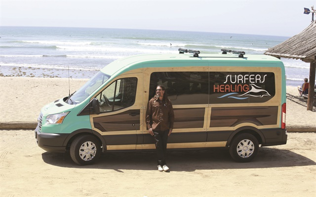 Izzy Paskowitz uses his 'woodie'-inspired Ford Transit to transport volunteers and equipment to his nonprofit's surf camps for autistic children. The van features a roof rack that can transport 10 tandem surfboards.