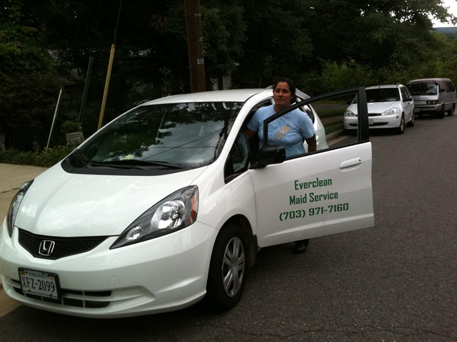 "An Everclean Maid Services supervisor standing with the recently purchased Honda Fit, one of seven vehicles in fleet that the company has put logos on in hopes to ""territorialize"" the company."