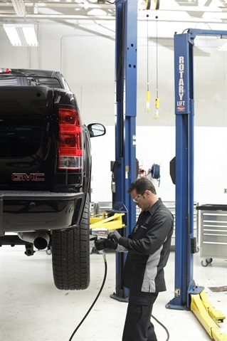 A GMC Cerified Technician performs a tire rotation — one component of the maintenance coverage included in Pro Grade Protection — on a 2013 Sierra 1500.