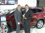 Wolski and Oldenburg pose in front of the Toyota Highlander Hybrid,