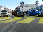 Two Ford Super-Dutys next to the new F-150 outside of the conventions