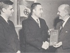 In 1963, Ed (center) accepts a plaque from Howard Pyle, president of